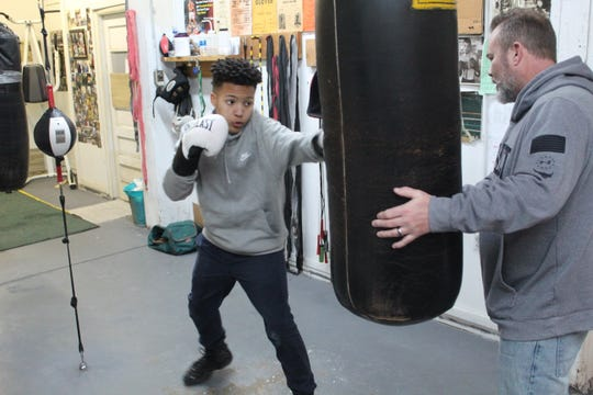 Elijah Karlovetz, left, hits the heavy bag with coach Joe Laughlin at Fremont Wreckers Boxing Club.