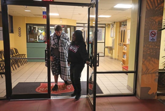 Todd Anderson, 21, leaves the reception area of Lee County's Salvation Army accompanied by Ramona Miller of Voice in the Wilderness after requesting an emergency bed as frigid temperatures moved in on Jan. 21. The local Salvation Army opened 30 extra cots for the cold front, 15 each for men and women. Miller found Anderson shivering outside a Fort Myers service station where he had come after being released from jail, homeless, five days before.