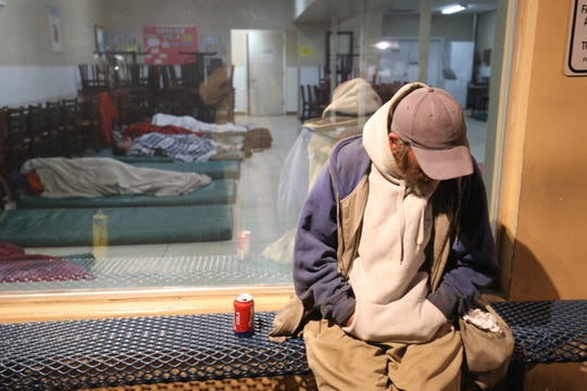 A man sleeps sitting up outside a local Salvation Army resource center in Fort Myers where 30 emergency beds have been added because of frigid temperatures on the night of Jan. 21. The Lee County Homeless Coalition estimated there were fewer than 300 beds for around 3,000 homeless people in 2018. Many of the emergency shelter beds in Lee County require the person to meet certain conditions such as having an addiction or mental health problem or be willing to observe Christianity.