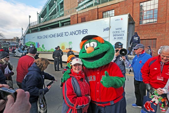 Red Sox fan Ellen Nichols of Holbrook got her photo taken outside Fenway Park in Boston with Wally the Green Monster during Red Sox Truck Day for the departure of the Red Sox equipment truck to the club's Spring Training home at JetBlue Park in Fort Myers. The celebration of Truck Day has been a Red Sox tradition since 2003 signaling the unofficial start of Spring Training.