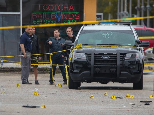 Fort Myers Police department and Florida Department of Law Enforcement at the scene of a shooting at Mahogany's Beauty Salon on the corner of Fowler Street and Hunter Street Saturday.  Police markers can  be seen by what looks like shell casings and a firearm, among other items. A man who was shot by police after he fired at them has died and a women police said the man shot, identified as his wife, remains in Lee Memorial Hospital.