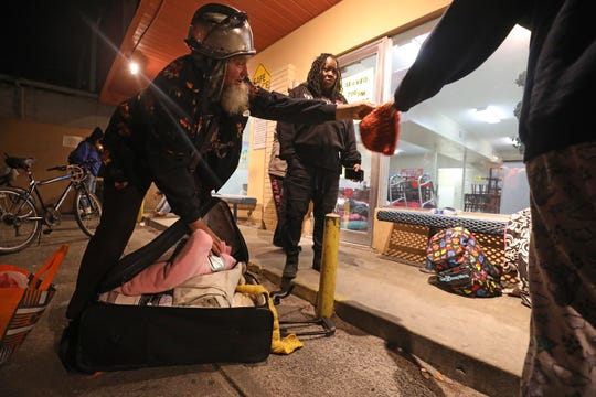 William Shotmiller gives out blankets to homeless residents of Lee County as temperatures plummet on the night of Jan. 21. The blankets were provided by St. Martin de Porres of Tice, a homeless cafe. With Shotmiller is Ramona Miller of a Voice in the Wilderness, also helping people on the streets. They are standing outside the local Salvation Army resource center in Fort Myers where 30 emergency beds have been added because of the cold.