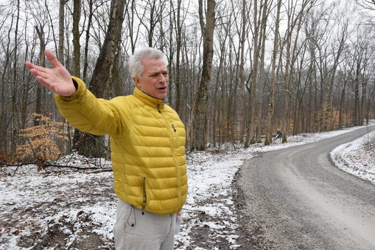 Jeff Stant, executive director of the Indiana Forest Alliance, stands near Hickory Ridge Trail 11 on Horse Camp Road, Friday, Jan. 31. At this location, Horse Camp Road would be the dividing point between land that would be burned to the east of the road (left) and land that would remain untouched to the west.