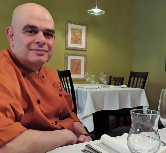 Chef David Zaghloul relaxes in Chez Grace, the upscale restaurant he founded in Coralville a decade ago. He has no staff, preferring to serve and cook for his customers entirely by himself.