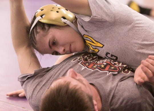 Fowlerville student Hannah Arledge-Teran wrestles with classmate Clayton Minock in practice at the high school Monday, Feb. 3, 2020.