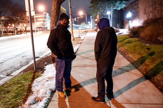 Bryan McGruder, with Projects in Assisting the Transition from Homelessness, left, talks with a homeless man on Grand Avenue in downtown Lansing. January 2020.