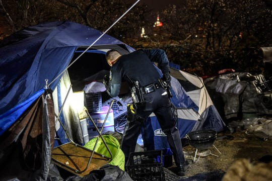 Lansing Police Officer Dillon Reust checks out a homeless camp near I-496 in January 2020.