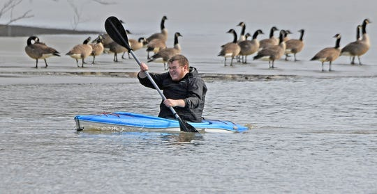 Alex Myers of Shelby paddles past a flock of geese standing on the ice in the Clear Fork Reservoir on Monday. Temperatures reached nearly 60 degrees and allowed outdoor enthusiasts to get some much-needed sun. The balmy February weather is not expected to last long as the National Weather Service is predicting a chance of rain, snow and freezing rain late Tuesday.