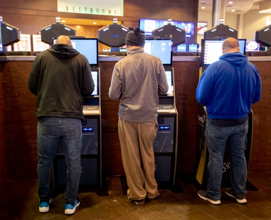 People use sports betting kiosks Feb. 3, 2020, at Southland Casino Racing in West Memphis.
