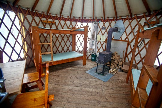 The Union Bay East yurt at Porcupine Mountains Wilderness State Park has two bunk beds, a table with four chairs and a wood-burning stove inside.