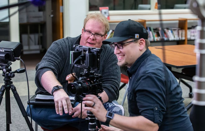 South Milwaukee High School alumni, Emmy winning filmmaker Kyle Olson, left, and freelance cameraman Nick Koscielniak, review footage during a commercial shoot at the school on Saturday, Feb. 1, 2020.