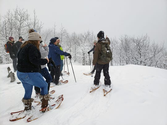 Katie Urban, right, talks to a group of snowshoers at the East Vista in Porcupine Mountains Wilderness State Park during a guided snowshoe through the park on Jan. 25, 2020.