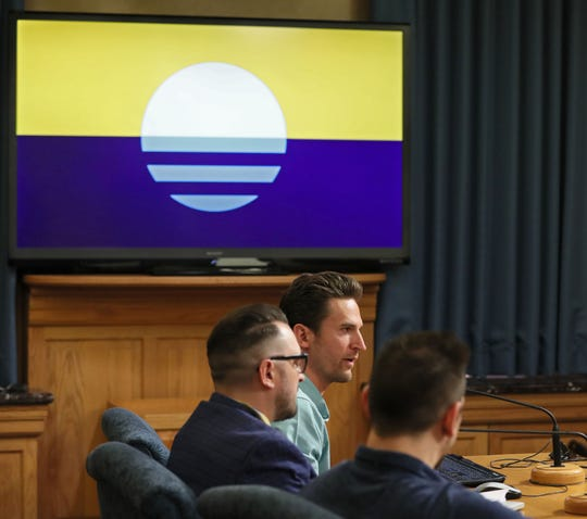 A committee of the Milwaukee Common Council hear from a group of graphic artists and individuals on what has become known as the People's Flag of Milwaukee.  In this photo, graphic designer Steve Kodis (rear) and the flag's designer Robert Lenz (second from rear) explain how the flag's design came about and what elements make for a modern flag design. The People's Flag is on the screen.