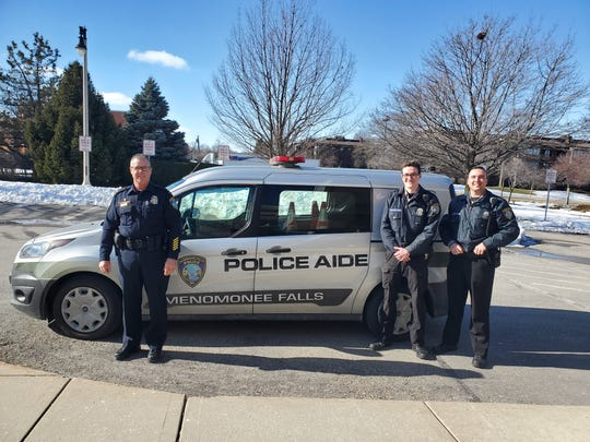 Menomonee Falls Police Lt. Mike Brasch (left) poses with two police aides, Dylan Braatz (center) and Connor Schmid in front of a police van. The police department has 14 part-time police aides who provide service to the community and gain career experience.