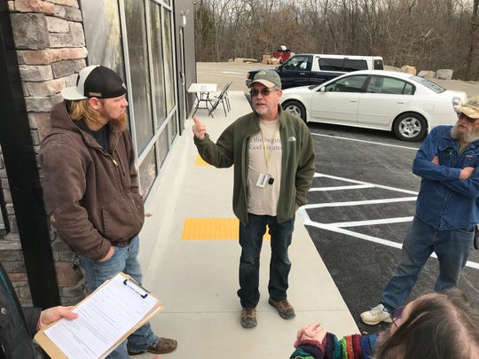Jeff McAnally, one of the co-owners of Plant Family Therapeutics, talks to would-be customers waiting in line for the marijuana dispensary to open Monday morning.