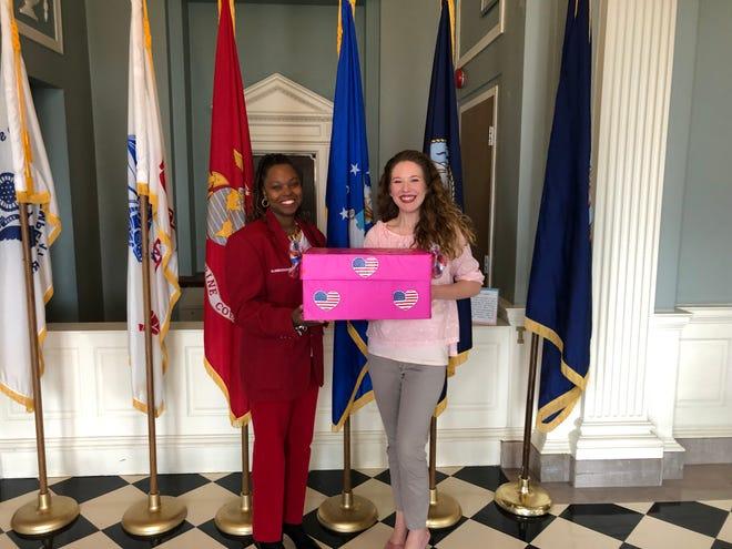 VA Ambassador Debbie, left, receives cards from Town of Pike Road Community Involvement Coordinator Katy Garren.