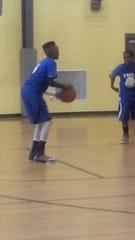 Justin Bufford, 12, shoot free throws at a YMCA basketball game.