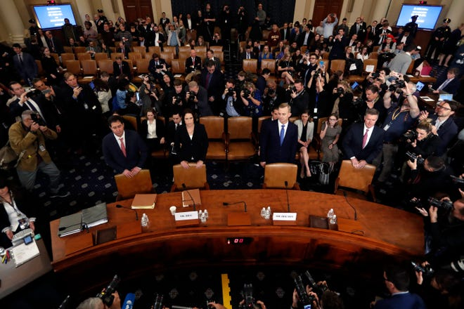 Former White House national security aide Fiona Hill, second from left, and David Holmes, a U.S. diplomat in Ukraine, stand behind their chairs as they arrive to testify before the House Intelligence Committee on Capitol Hill in Washington, Thursday, Nov. 21, 2019, during a public impeachment hearing of President Donald Trump's efforts to tie U.S. aid for Ukraine to investigations of his political opponents.