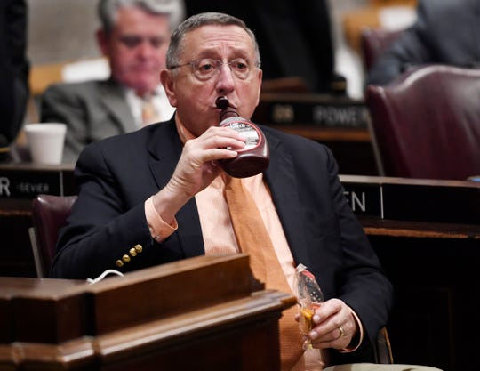 Rep. Kent Calfee, R-Kingston, drinks out of a chocolate syrup bottle as he waits for the start of the State of the State address at the state Capitol Monday, Feb. 3, 2020 in Nashville, Tenn.