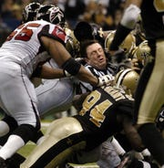 Umpire Jeff Rice of Fort Myers is sandwiched by a group of New Orleans Saints and Atlanta Falcons players in the second quarter in the Louisiana Superdome in New Orleans, Sunday, Dec. 26, 2004. The hit forced Rice out of the game with a gash on his forehead.