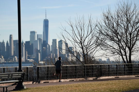 A runner jogs in shorts along the Hudson River during an unseasonably warm day in Weehawken Monday, Feb. 3, 2020. Temperatures were in the high 50s in North Jersey.