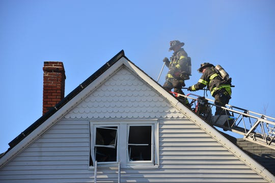 Firefighters climb the roof of a burning home on Clinton Place in Hackensack on Feb. 3.