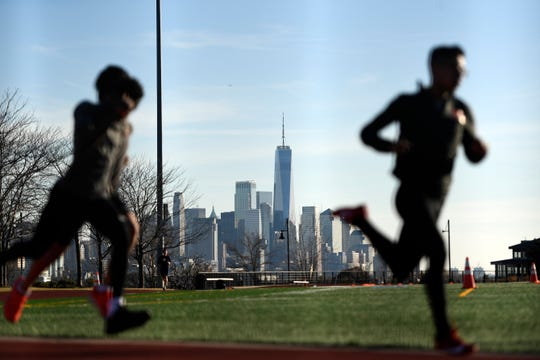 Runners sprint around a track in Weehawken, NJ with the lower Manhattan skyline in the distance as North Jersey experiences temperatures in the high 50s on Monday, Feb. 3, 2020.