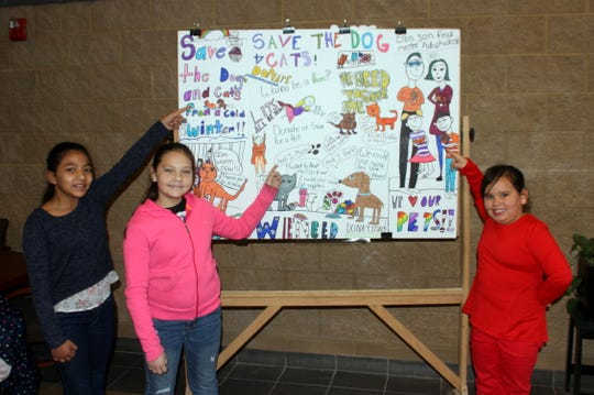 Three students at Bataan Elementary School in Deming, NM have constructed a poster board for the school's front lobby in hopes of collecting pet supplies to be donated to animal shelters and rescues in Luna County. Pet food, towels, laundry supplies, blankets and pet toys can be brought to the school for donations. Pictured from left are poster board creators fourth grader Marissa Edwards, fifth grader Emily Chavez and third grader Jade Duffy.