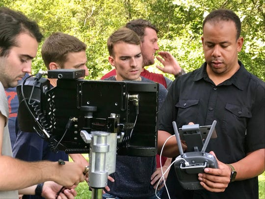 Kyle Clinton (middle) looks over a just-processed clip.