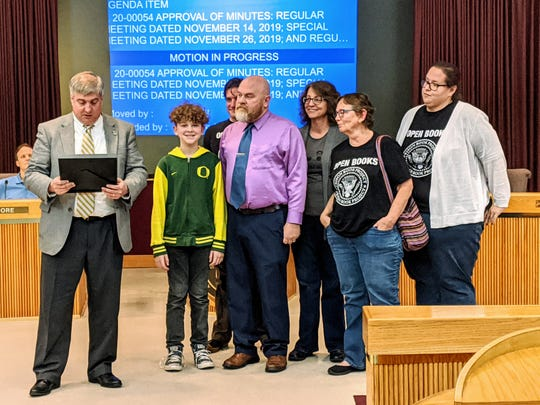 Mayor Grover Robinson reads the official proclamation document as volunteers Christopher Scott Satterwhite along with his son Desmond, Dale Welch, Joann Massey, Terry Covington and Sara Ratliff receive the honor on behalf of the Prison Book Project.