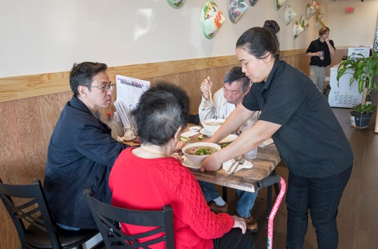 Pho Real co-owner Nina Truong, right, delivers an order to a table at the restaurant on North Davis Highway in Pensacola on Monday.
