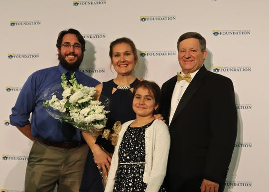 Cheyenne Novotny, center, a science teacher at West Florida High School was announced as the 2020 Escambia County School District's Teacher of the Year at the Escambia County Public School Foundation's Golden Apple Dinner on Friday at New World Landing. She is pictured with her husband, at left, their daughter and Superintendent Malcolm Thomas.
