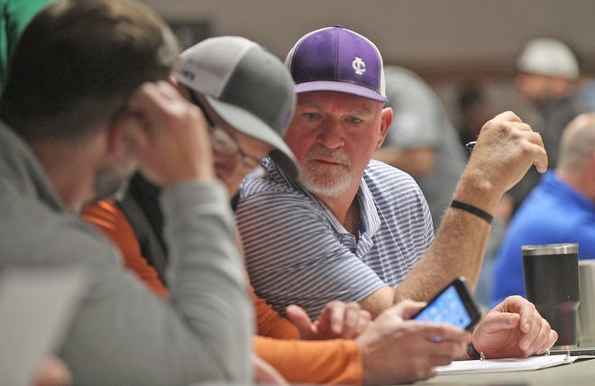 Irion County head football coach Don Coffell, center, examines the results of the UIL realignment at the Region 15 Service Center in San Angelo on Monday, Feb. 3, 2020.