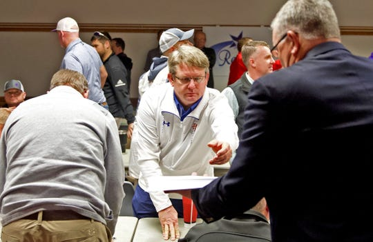 Central High School football coach Brent Davis, center, receives the results of the UIL realignment at the Region 15 Service Center in San Angelo on Monday, Feb. 3, 2020.
