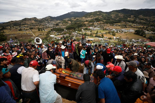 Mourners lower the coffin of community activist Homero Gomez Gonzalez into a grave at a hillside cemetery, in Ocampo, Michoacan state, Mexico on Jan. 31.