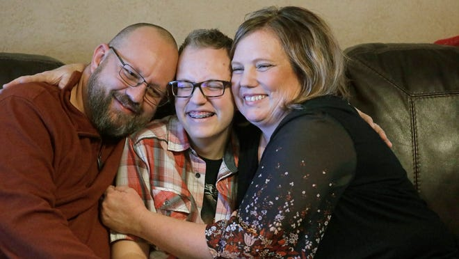 Dex Rumsey, 15, is photographed with his mother Robyn and father Clay Friday, Jan. 17, 2020, in Roy, Utah. Dex Rumsey, 15, came out as transgender at age 12. In consultation with a counselor and doctors, he gradually began wearing short hair and boy's clothes, then began using puberty blockers and eventually testosterone. He is scared he could become depressed and suicidal again if a ban on hormone therapy and sex-reassignment surgery for minors were to pass.