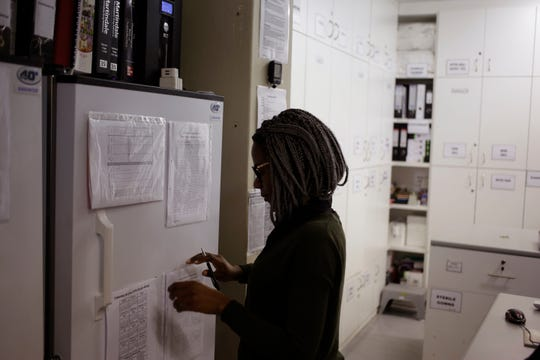 In a Nov. 30, 2016 file photo, pharmacist Mary Chindanyika looks at documents on a fridge containing a trial vaccine against HIV on the outskirts of Cape Town, South Africa.