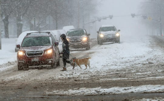 A dog walker crosses the road, Monday, Feb. 3, 2020, in Salt Lake City, Utah, after a winter storm dropped over a foot of snow in parts of the valley.
