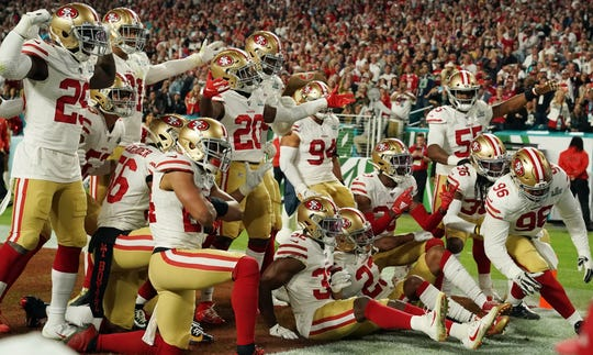 San Francisco 49ers players celebrate after an interception.