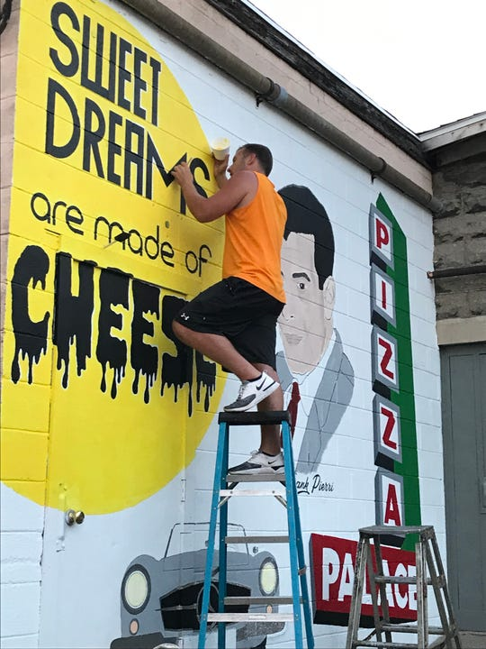 Riley Brice, founder Frank Pierri's grandson, will reopen the restaurant later this spring. In this July photo, he is shown painting a mural in honor of his grandfather on the building's alley side.