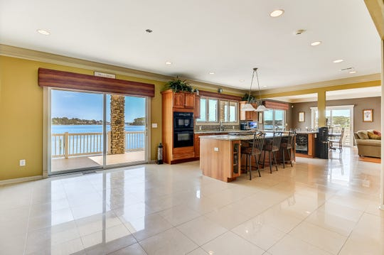 The gourmet kitchen offers an oversized granite island and wine cooler.