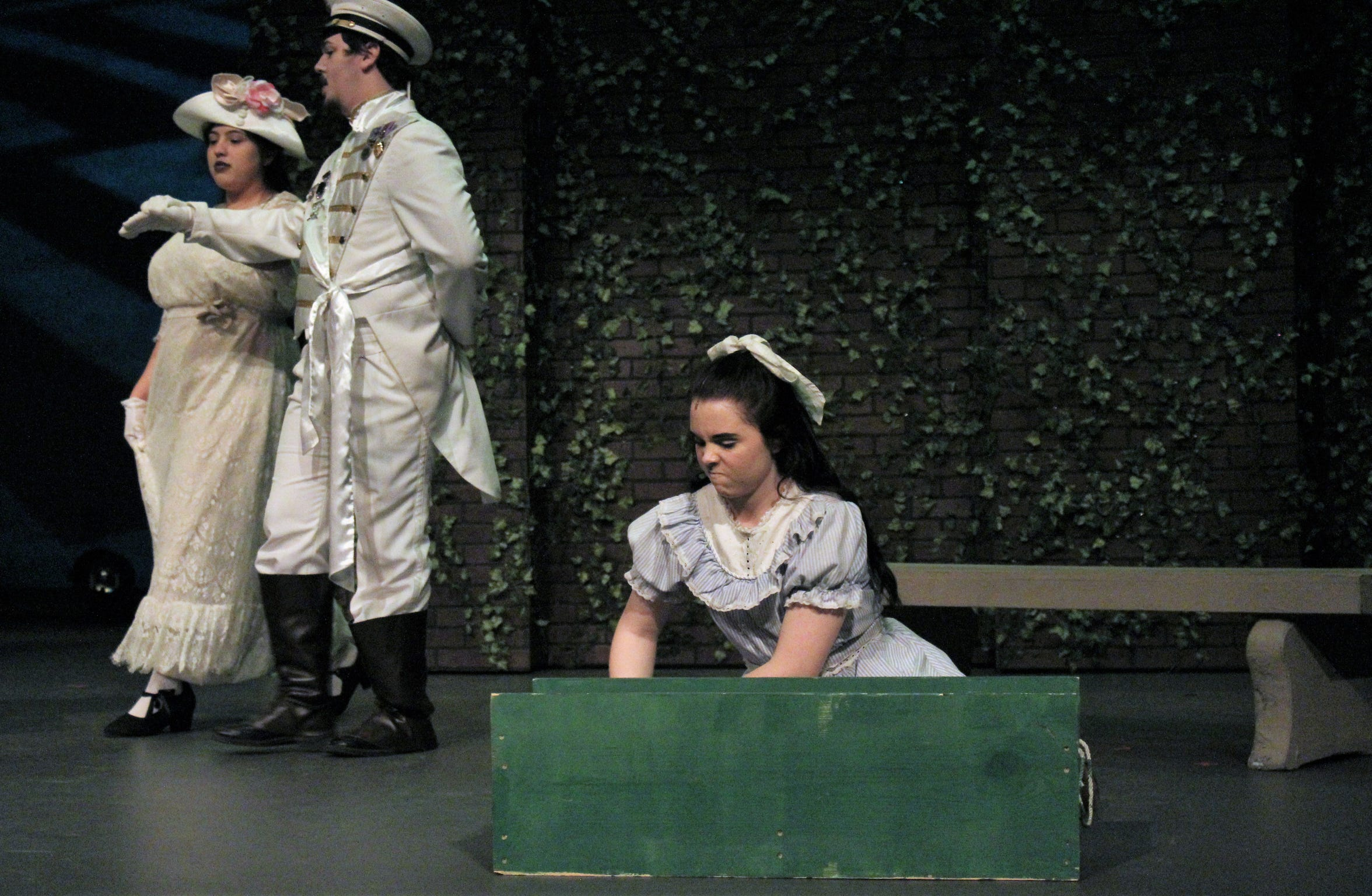 """A not-so-happy Mary (Shelby Walker) grimaces while playing in a sandbox in this rehearsal scene from """"The Secret Garden."""""""