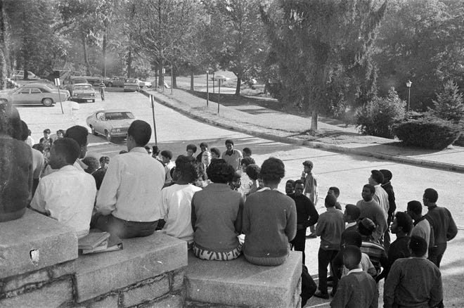 Black and white images taken by Roger Ball in Sept. 1969 during and after a school walkout by many African American AHS students. Asheville High School Principal Clark Pennell talks with students who had walked out of the school in protest of poorly supported African American concerns in 1969. Ball had been the school photographer and had been asked by Pennell to document what was to take place.