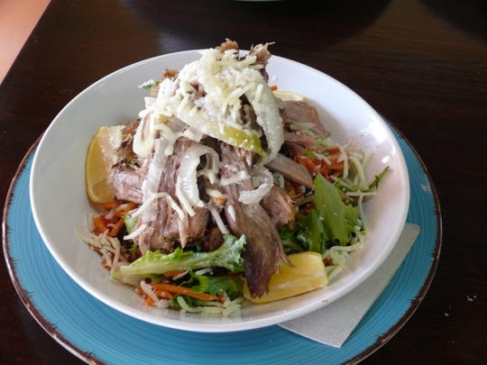 Lechoncito Salad at Nini's in Suntree features roasted pulled pork with plenty of mojo, plus onions, mixed greens, tomatoes, carrots and cucumbers, served with Nini's house vinaigrette.