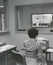 Mrs. Clara Hurles, clerk, out patient office, is shown at work in this picture taken in the office and looking across the lobby into the general chemistry lab. From the Aug. 20, 1960 Gazette.