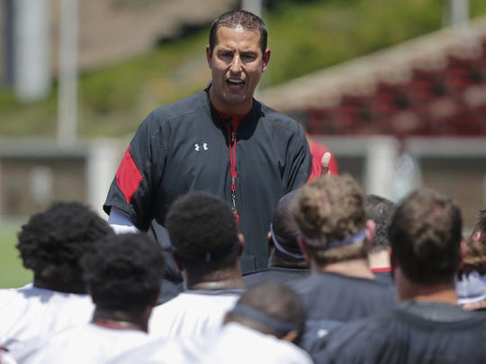 Cincinnati Bearcats head football coach Luke Fickell instructs the team after stretching during Cincinnati Bearcats training camp practice on July 26, 2017, at Nippert Stadium.