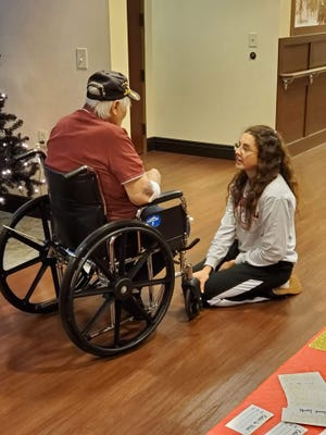 A girl involved with the new Clarksville nonprofit The Kindness Objective speaks with a veteran during an event at the Tennessee State Veterans' Home in December.