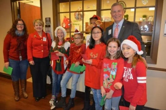 Clarksville Mayor Joe Pitts poses for a photo with children who attended the holiday party held by The Kindness Objective in December at the Tennessee State Veterans' Home in Clarksville.