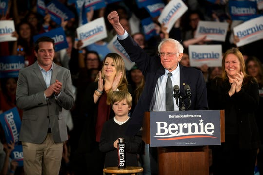 Vermont Senator and 2020 Democratic presidential candidate Bernie Sanders speaks with his family on stage during his Caucus Day rally on Monday, Feb. 3, 2020, in Des Moines.