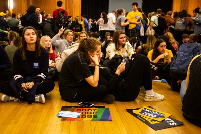 University of Iowa students Sophia Sear and Julia Krischel, both 18, of Minneapolis, Minn., sit on the floor together with Pete Buttigieg supporters during a realignment period caucus, Monday, Feb. 3, 2020, at the Iowa Memorial Union in Iowa City, Iowa.